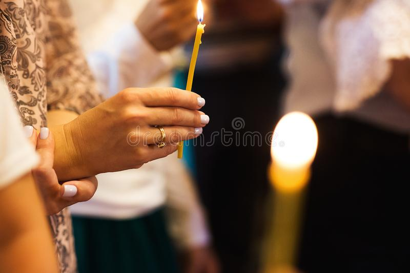 Close up somebody`s hands set fire to a wax candle in the church royalty free stock photography