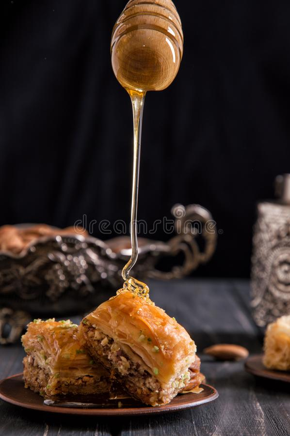Close up. Someone is holding honey dipper and pours viscous honey on the freshly baked oriental baklava. Black background royalty free stock photography
