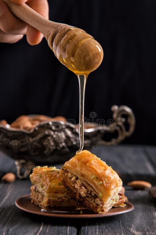 Close up. Someone`s hand is holding honey dipper and pours fragrant honey on the freshly baked oriental baklava. Black background stock photo
