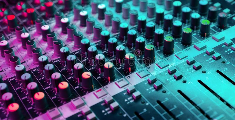Close up of sound mixing console. Details of sound engineer room. Neon light.  royalty free stock photo