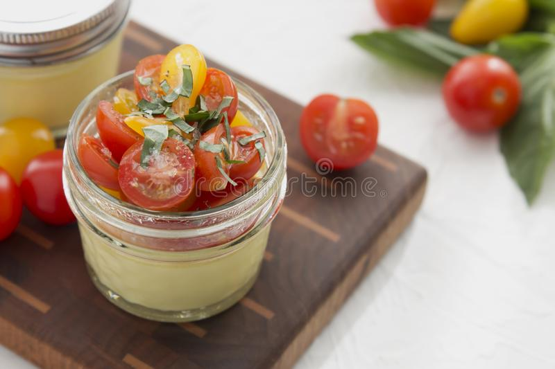 Close-up Sous Vide Egg Bite. Close-up on a Sous Vide Egg Bite in glass jars with tomatoes and fresh basil stock images