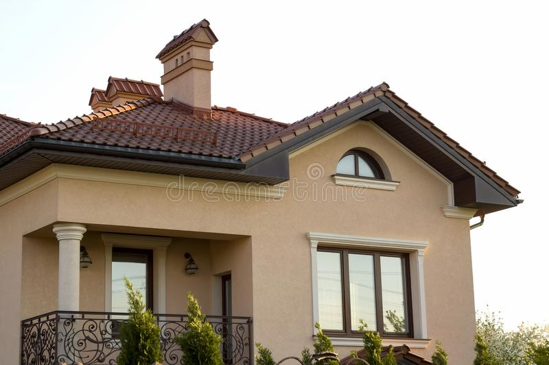 Close up of spacious brown shingle roof of modern luxurious expensive residential cottage house with three chimneys, big windows royalty free stock photos