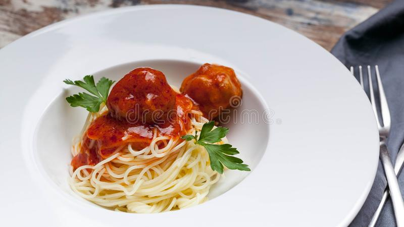 Close-Up spaghetti and meatballs in tomato sauce on a white plate royalty free stock photography