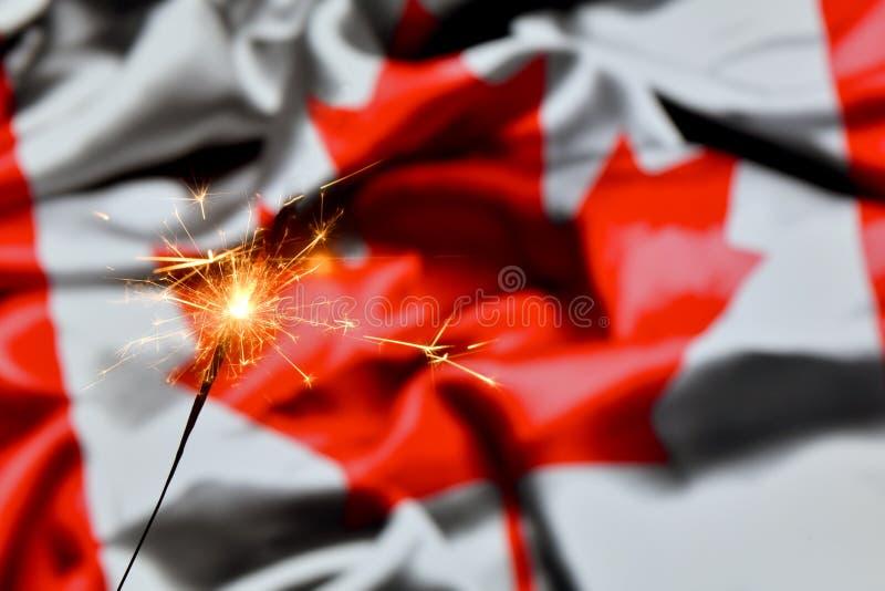 Close up of sparkler burning over Canada, Canadian flag. Holidays, celebration, party concept. stock photo