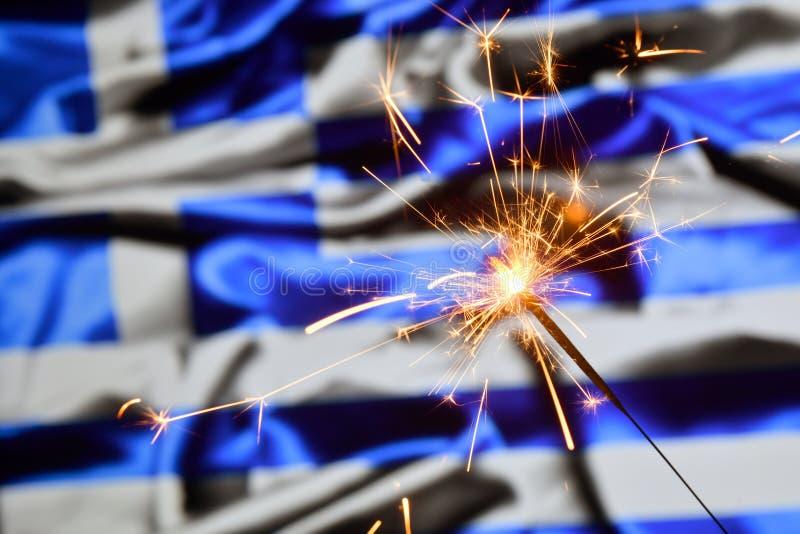 Close up of sparkler burning over Greece, Greek flag. Holidays, celebration, party concept. Close up of sparkler burning over Greece, Greek flag. Holidays stock photo