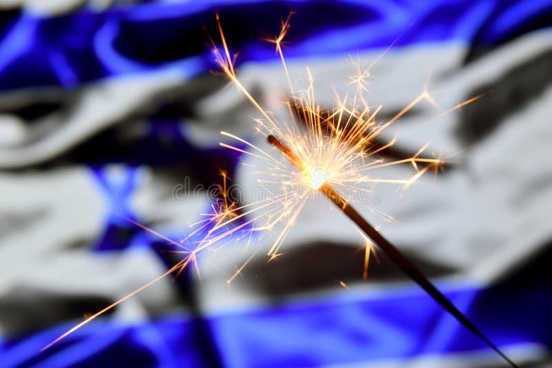 Close up of sparkler burning over Israel, Israeli flag. Holidays, celebration, party concept. Close up of sparkler burning over Israel, Israeli flag. Holidays royalty free stock images