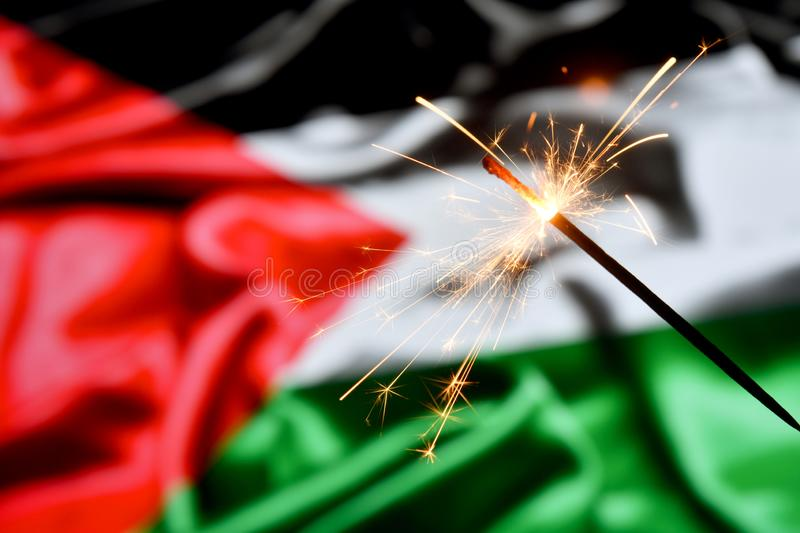 Close up of sparkler burning over Palestine, Palestinian flag. Holidays, celebration, party concept. Close up of sparkler burning over Palestine, Palestinian stock photography