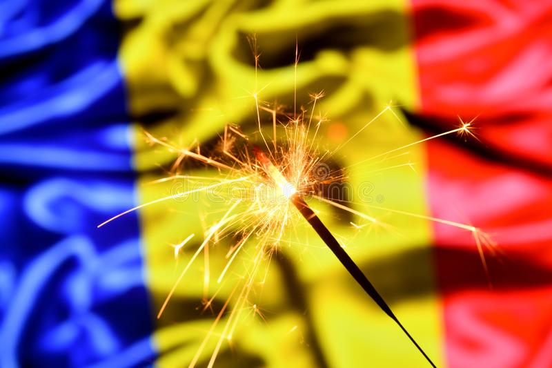 Close up of sparkler burning over Romania, Romanian flag. Holidays, celebration, party concept. Close up of sparkler burning over Romania, Romanian flag royalty free stock photo