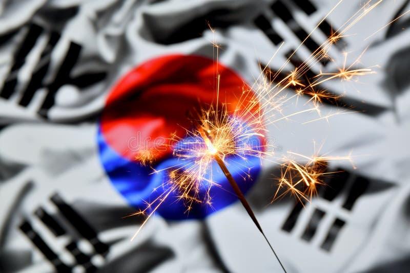 Close up of sparkler burning over South Korea, Korean flag. Holidays, celebration, party concept. Close up of sparkler burning over South Korea, Korean flag royalty free stock photo