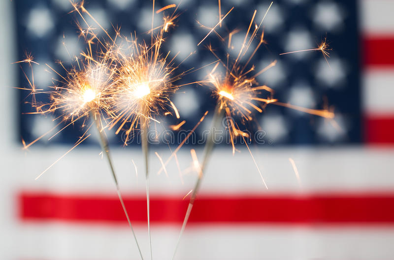 Close up of sparklers burning over american flag. American independence day, patriotism, holidays and celebration concept - close up of sparklers burning over royalty free stock images