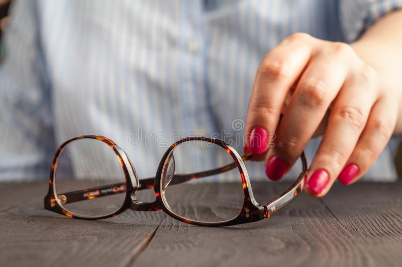 Close up spectacles with girl hand holding glasses on wood desk. Release concept. spectacles selective focus stock photo