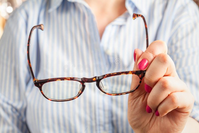 Close up spectacles with girl hand holding glasses on wood desk. Release concept. spectacles selective focus royalty free stock photos