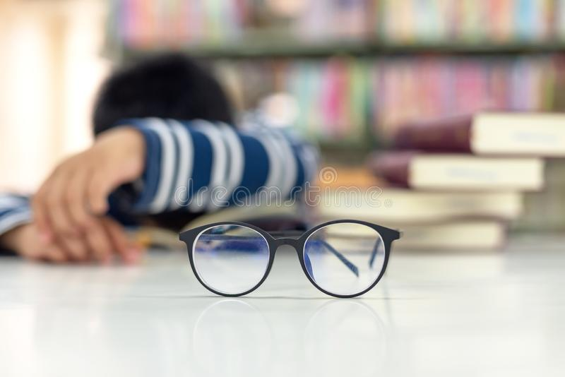 Close up spectacles. Schoolboy sleeping on books, kids tired reading for education and go to school in library royalty free stock photos