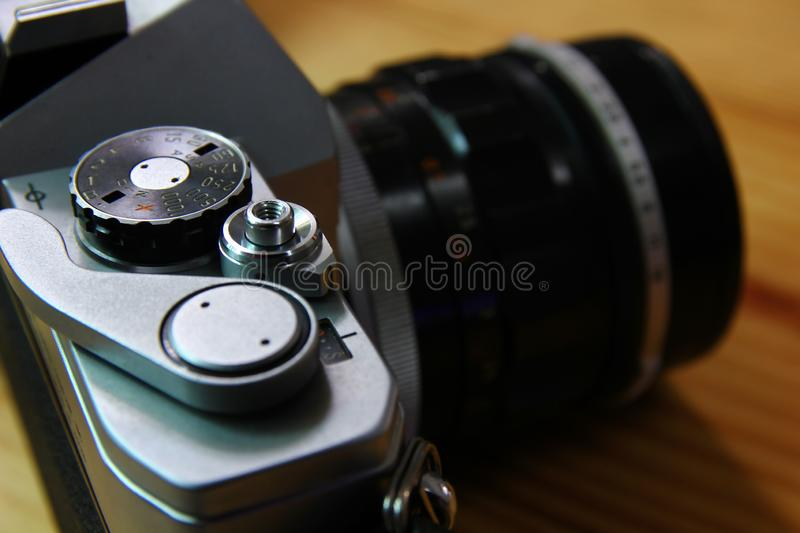 Close up the speed shutter button of camera film on wood floor,grain in photo is still a charm of the olden days technology. Close up the speed shutter button of royalty free stock photo