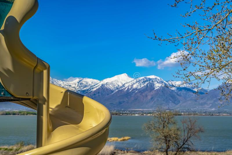 Close up of a spiral slide at a sunny playground with view of a lake. A mountain with snowy peaks against rich blue sky cna be seen in the distance royalty free stock photos