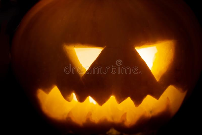 Close-up of Spooky and laughing carved Halloween Jack-o-lantern. Pumpkins with lights isolated over dark background stock photo