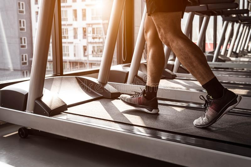 Close up of sport man running on treadmill in fitness gym at condominium in urban. People lifestyles and sport activity concept.  stock photos