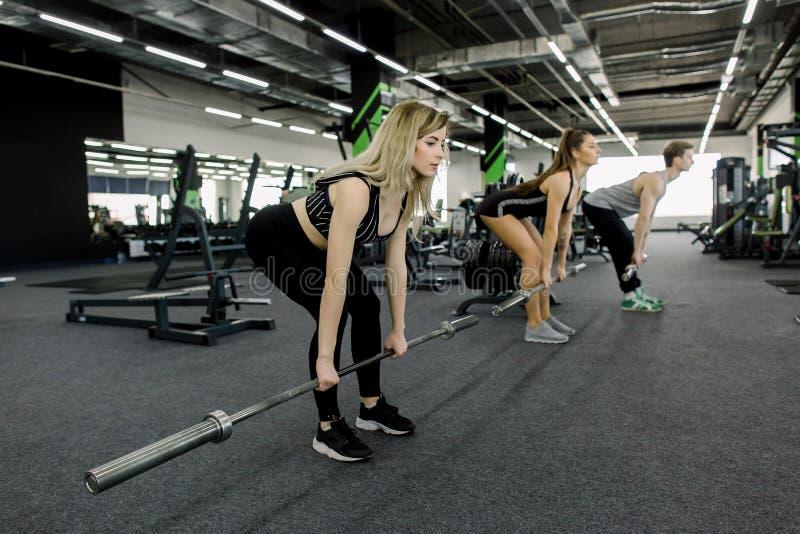 Close-up - Sportieve Atletische Man en Vrouwen die met Barbells opleiden Dwars geschikte opleiding Jongeren tijdens Training in G stock afbeeldingen