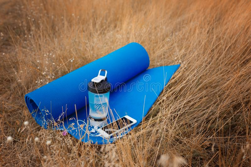 Close-up sports items. Mat, bottle of water and a phone on a natural background. Outdoors training concept. Copy space. Close-up of a saturated blue sports mat stock photo