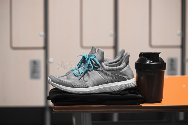 Close up of sports shoes, sportswear and sport water bottle in gym locker room royalty free stock image