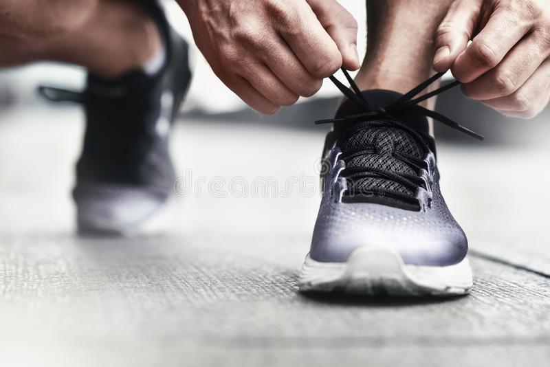 Close-up of sportsman tying sneakers. Unrecognizable man stopping lacing shoe outdoors. Athletic shoes concept. Color Version royalty free stock photography