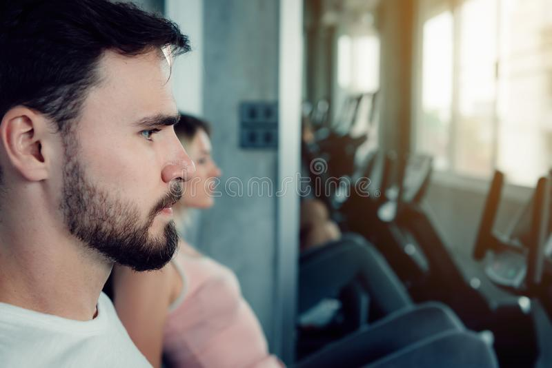 Close-up of sporty couple exercised stationary bicycles in fitness gym., Portrait of people group training workout on cycling royalty free stock photos