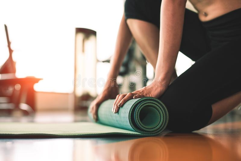 Close up of sporty woman folding yoga mattress in sport fitness gym training center background. Exercise mat rolling keeping after. Yoga class. Workout and stock photo