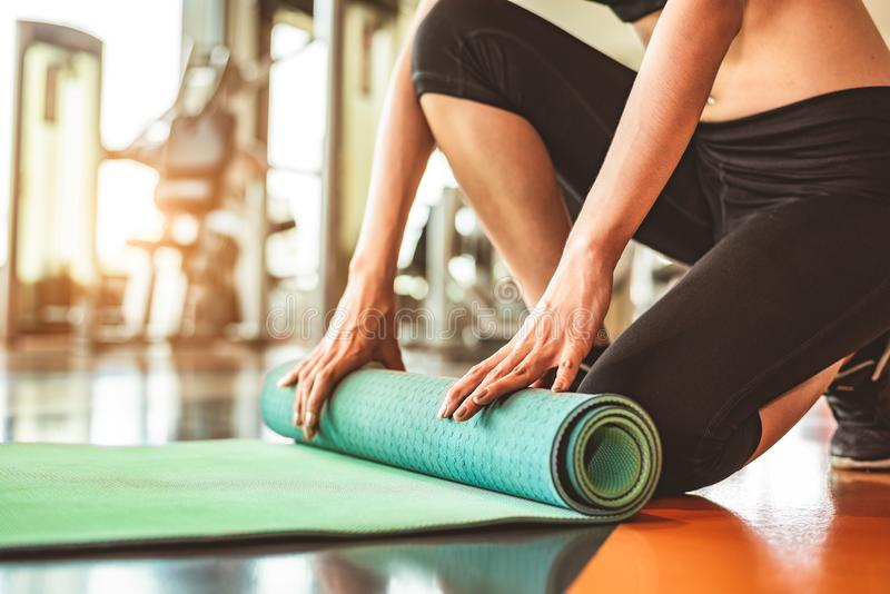 Close up of sporty woman folding yoga mattress in sport fitness gym training center background. Exercise mat rolling keeping after. Yoga class. Workout and royalty free stock image