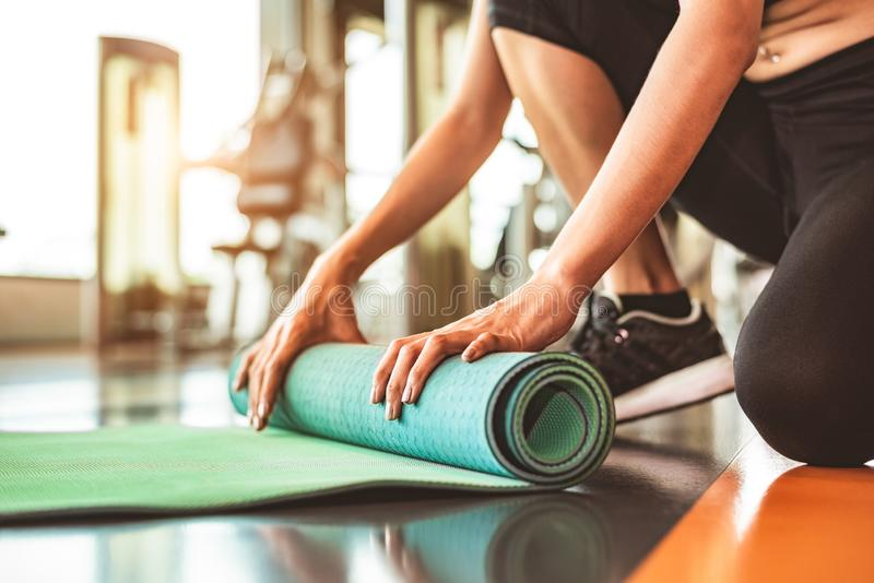 Close up of sporty woman folding yoga mattress in sport fitness gym training center background. Exercise mat rolling keeping after. Yoga class. Workout and stock photography