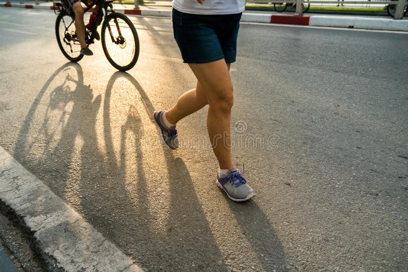 Close-up of sporty woman running on the road in the City park against a beautiful orange sunrise in early morning royalty free stock image