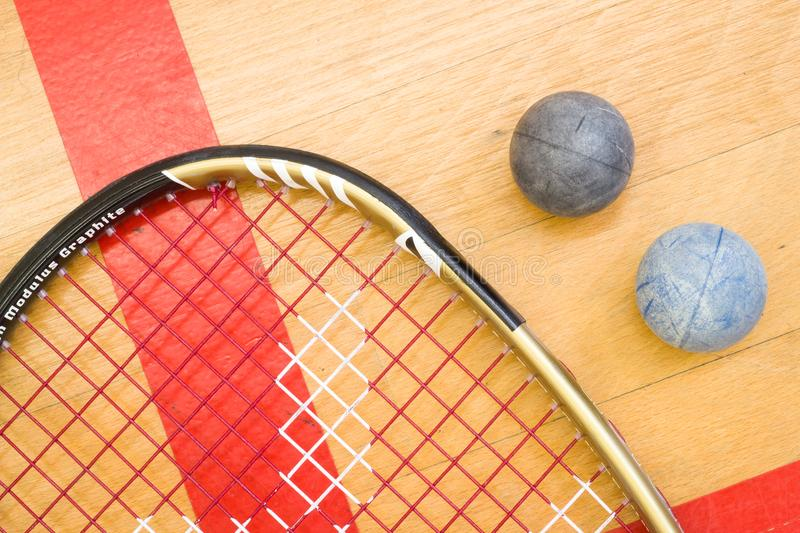 Close up of a squash racket and ball on the wooden background stock images