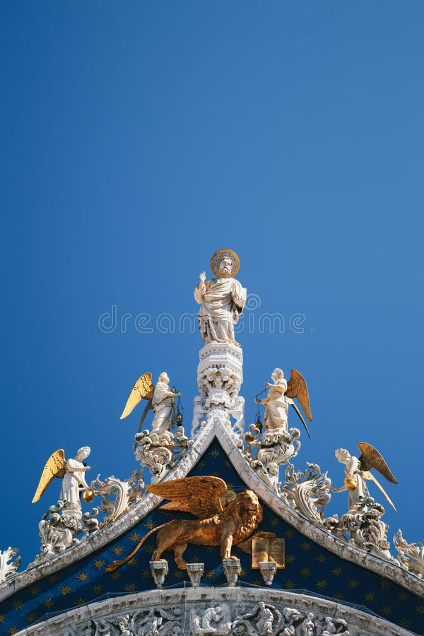 Close up of St Mark`s Apostle, angels and golden lion on the top of Basilica di San Marco, St Mark`s Basilica in Venice royalty free stock photo