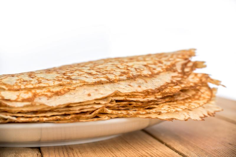 Close up on a stack of crepes french pancakes on a plate, white background royalty free stock photography