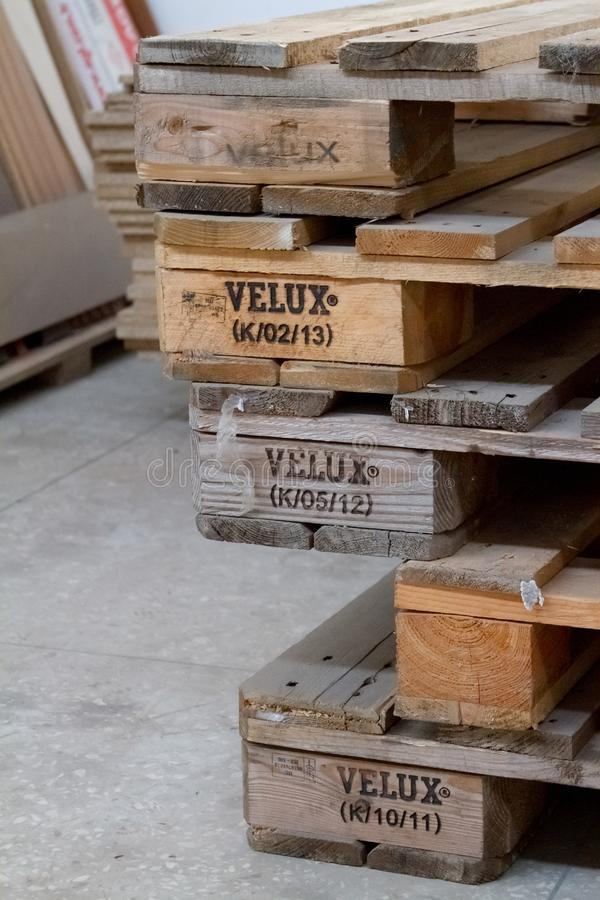 Close-up stack of shipping pallets with Velux inscription lying on the cement floor, selective focus royalty free stock image