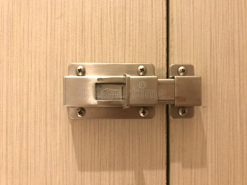 Close up stainless door bolt on the wooden toilet door. Stainless door bolt on the wooden toilet door stock images