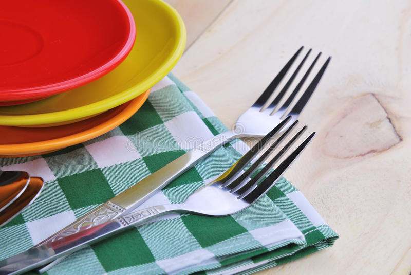 Close-up of stainless fork and spoon on table. Cloth with red,yellow, orange plate royalty free stock photo