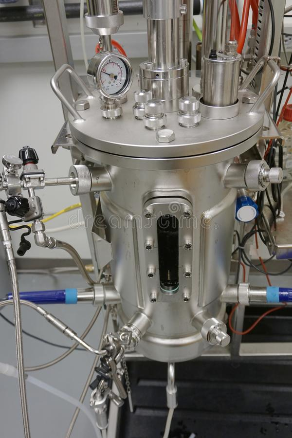 Close-up of a stainless steel bioreactor used to grow bacteria. Growing bacteria for large-scale, biotechnology applications using a stainless steel fermentor stock image