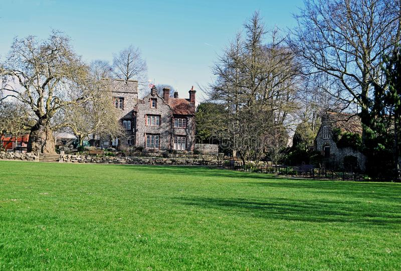 Close up of a Stately home in its magnificent gardens. Large tree on a grass lawn in front of a stately house in West gate gardens Canterbury Kent England stock photography