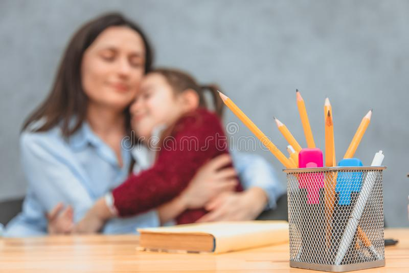 Close-up stationery set on the table. On the background of mother and daughter who embraced herself. Broken. Gray. Close-up stationery set on the table. On the royalty free stock photography