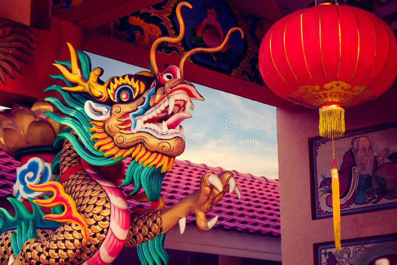Close-up statue of a dragon wrapped around a pole with Chinese lantern in Chinese temple. stock image