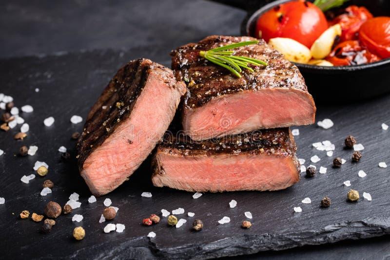 Close-up of steak Top Blade roasting medium ready to eat on dark stone background stock photography