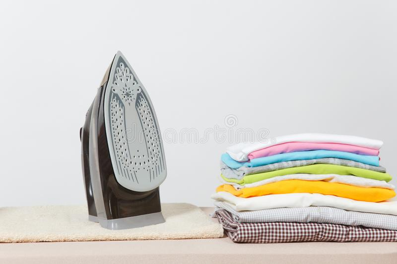 Close up steam iron colorful clothes washed laundry on white background. Housekeeping. Copy space advertisement. Place for text. Close up steam iron, ironing stock photos