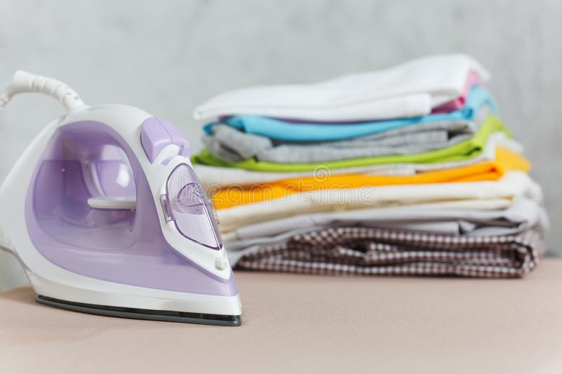 Close up steam iron colorful clothes washed laundry on white background. Housekeeping. Copy space advertisement. Place for text. Close up steam iron, ironing stock images