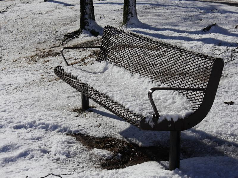 Steel bench covered with snow by the pond. Close up of a steel bench covered with snow royalty free stock photography