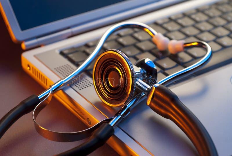 Close up of stethoscope on laptop. Medical stethoscope draped over a laptop keypad in orange stock image