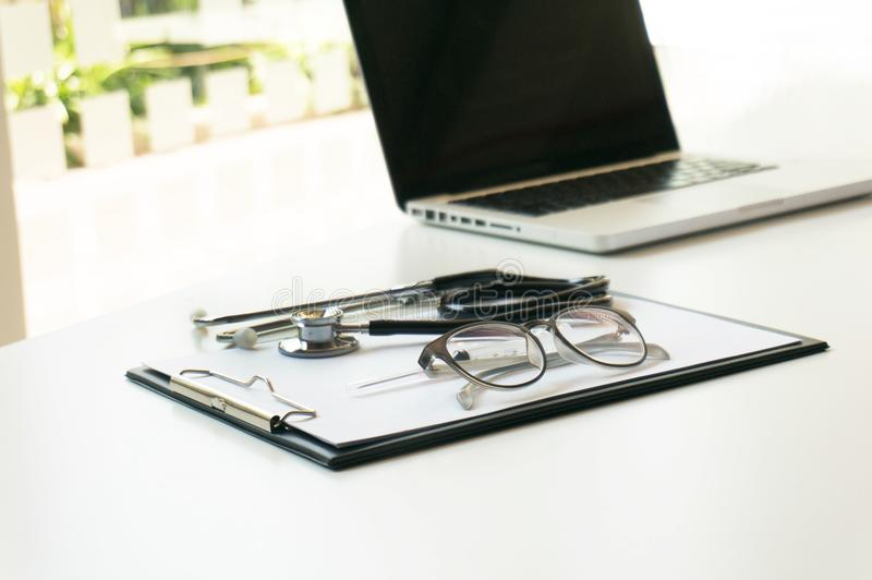 Close-up of stethoscope, paper, laptop on doctor table. selective focus. royalty free stock photos