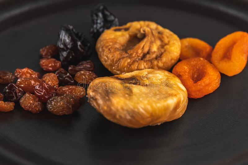Close-up still life background made with different dried fruits as dried apricots, raisins, prunes, figs, healthy eating concept, stock photo