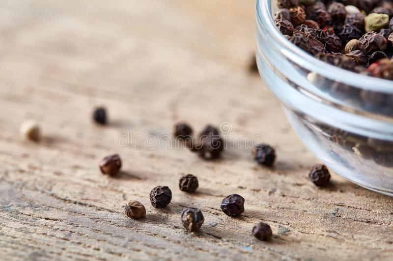 Close-up still life with black pepper seeds in glass jar on wooden barrel, shallow depth of field. royalty free stock image