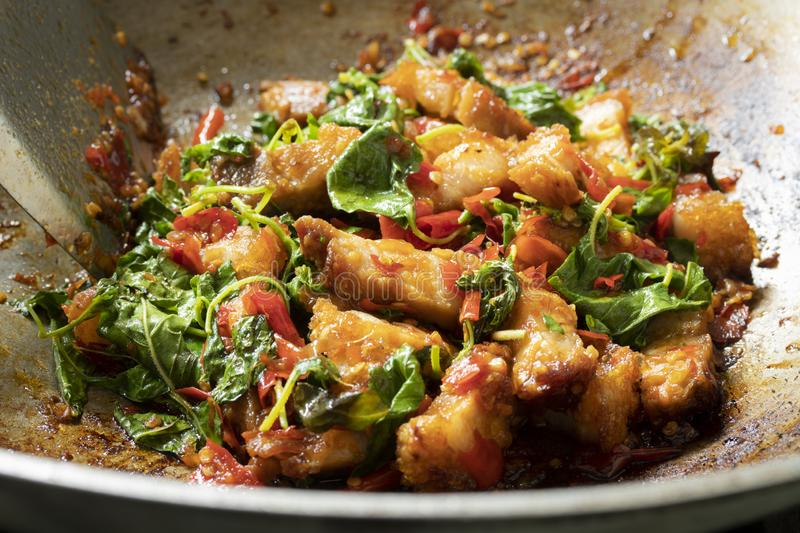 Close up of stir fried crispy pork with holy basil leaves in wok stock image