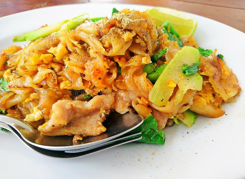 Close up Stir fried flat noodle and pork Thai Food royalty free stock image